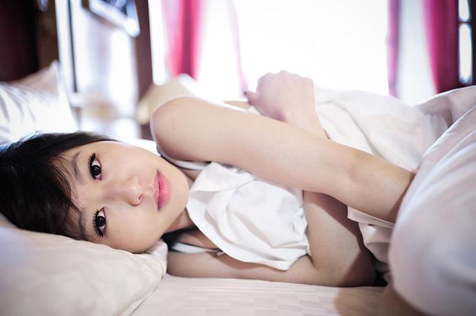 不安な表情でベッドに横になる女性