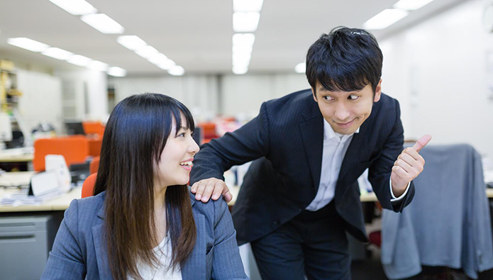 会社で同僚の女性を誘う男性