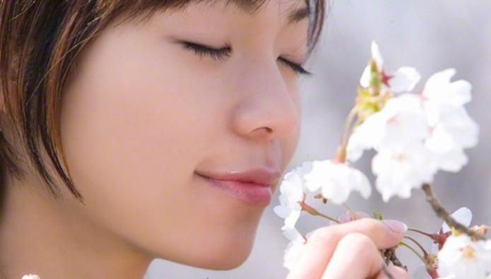 花のニオイを嗅ぐ女性