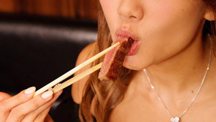 焼き肉を頬張る女性